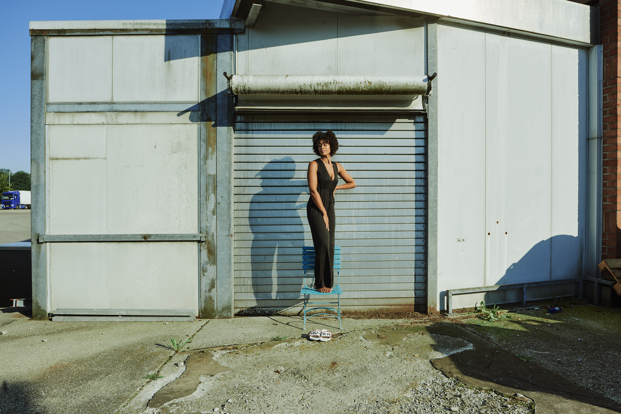 Young black woman poses like a statue in a backyard